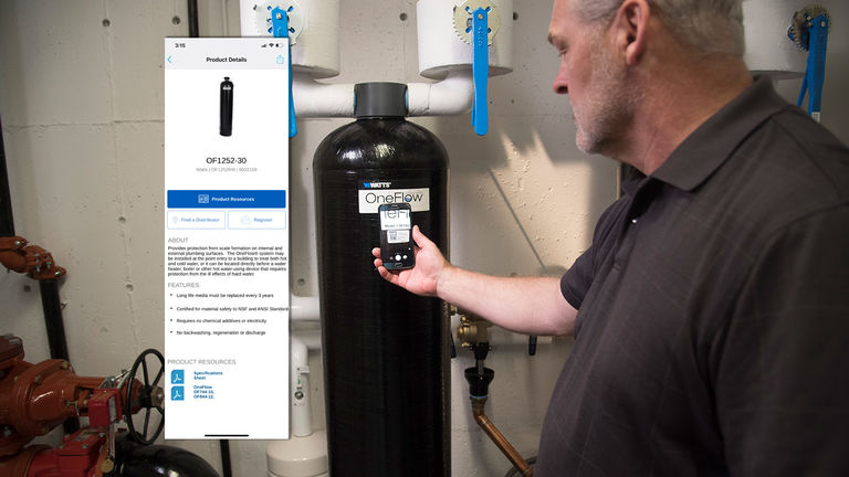 A man uses the Watts App to find more information about an installed OneFlow® product